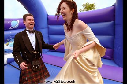 Bide in gold wedding dress and Groom in a kilt on a Bouncy Castle